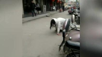 闹矛盾她当街跪地爬行,一男子跟随